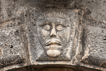 Bas-relief with man's face on ancient house facade in Perast