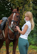 Nice blond girl with brown horse in autumn woods
