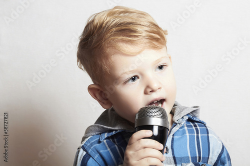 little boy singing in microphone.child karaoke.fashion haircut