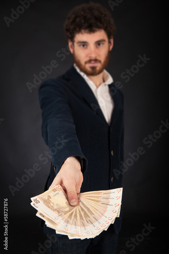 Young man showing euros banknotes against black background.