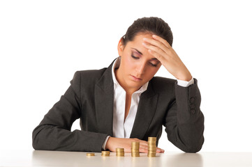 Worried businesswoman with stacks coins against white background