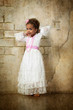 Beautiful mulatto girl in white dress on wall background.
