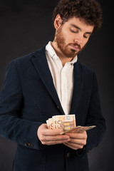 Young man counting euros banknotes against black background.