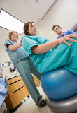 Nurse Assisting Pregnant Woman Sitting On Exercise Ball