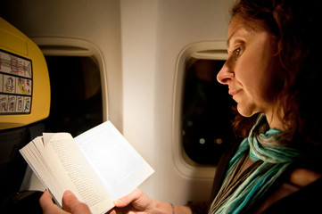 Woman reading book while voyaging in a plane.
