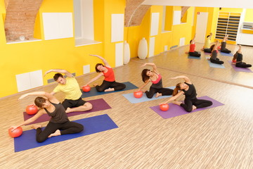 Aerobics pilates class with yoga balls in a row on fitness class