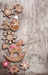 Gingerbread cookies lies over wooden background.