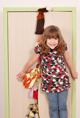 little girl trying to close the closet