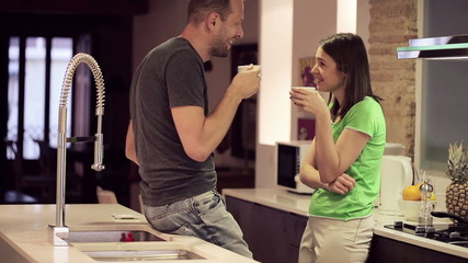 Young couple talking and drinking tea in kitchen at home