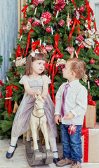 Small boy and the girl play near a beautiful Christmas fir-tree