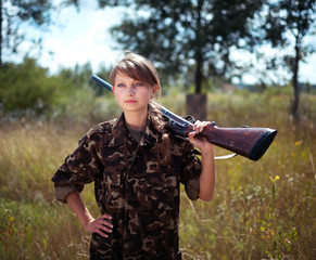 Young beautiful girl with a shotgun looks into the distance