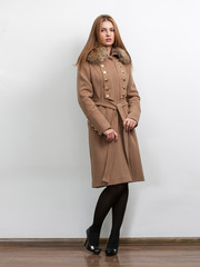 Sexy slim woman wearing long brown classic coat at studio