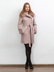 Sexy woman in pink classic coat posing against white background