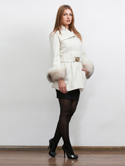 Sexy young woman wearing white coat with fur sleeves