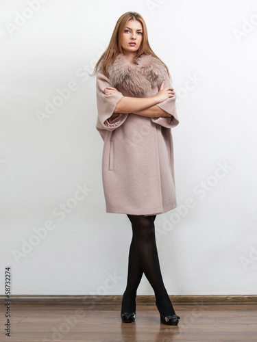 woman wearing beige long coat with fur collar and holding hands