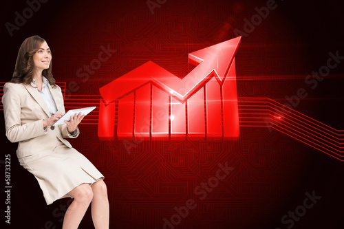 Composite image of businesswoman holding tablet and looking up