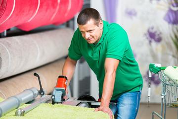 mitarbeiter schneidet teppich für kunden ab