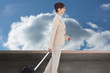 Composite image of serious businesswoman pulling suitcase
