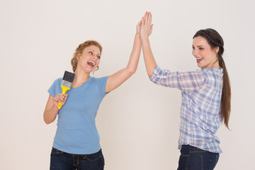 Two cheerful young female friends giving high five