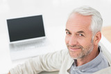 Close-up portrait of a grey haired man with laptop
