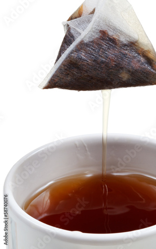 removing of tea bag from mug with brewing tea