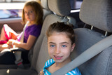 Kid girls with safety belt in car indoor