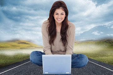 Composite image of woman sitting on the bed with the laptop in f