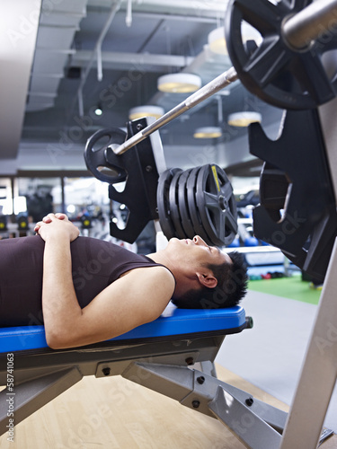 man lying on weight bench in fitness center
