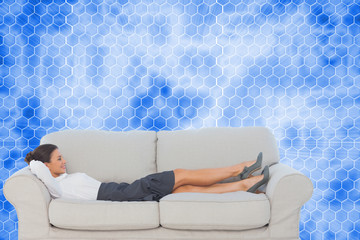 Composite image of smiling business woman lying down on the couc