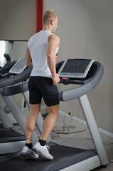 Blond young man running on treadmill