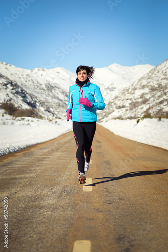 Cold winter woman running in road