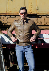 Attractive young man in leather jacket in front of old train