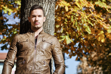 Handsome young man against tree in fall