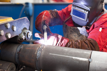 Welder working in a steel factory with sparks flying
