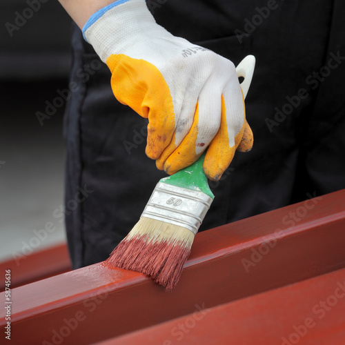 Worker painting steel tube with paint brush focus on hand