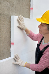 Female worker place styrofoam sheet insulation to the wall