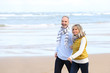 Senior couple walking on the beach in winter time - 58746068