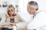Fototapety Doctor giving medicine to senior woman for arthritis pain