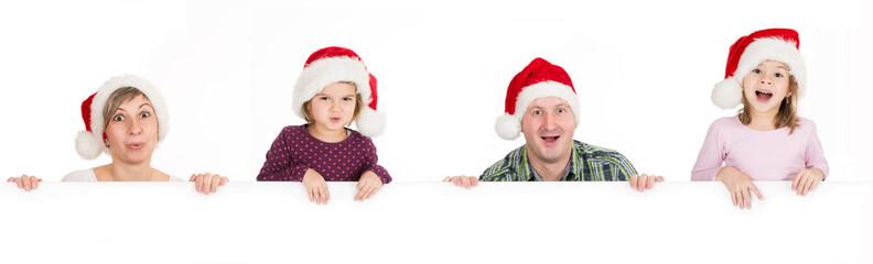Staunende Familie mit Werbeschild an Weihnachten