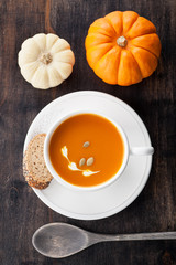 Pumpkin soup with pumpkin seeds in a white cup