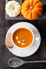 Pumpkin soup with pumpkin seeds in a white cup and raw pumpkins