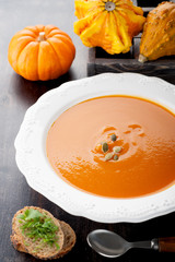 Pumpkin soup and raw pumpkins in wooden box