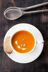 Pumpkin soup with pumpkin seeds in a white mug