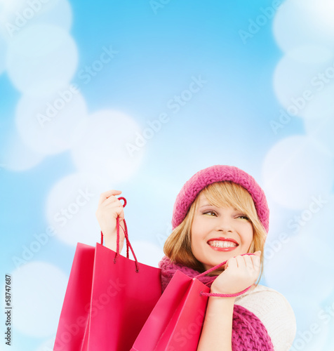 woman in pink hat and scarf with shopping bags
