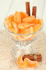 Tasty mandarine's slices in glass bowl on light background
