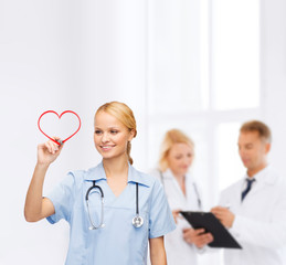 smiling doctor or nurse drawing red heart
