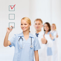 doctor or nurse drawing checkmark into checkbox