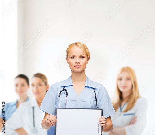 smiling female doctor or nurse with sclipboard
