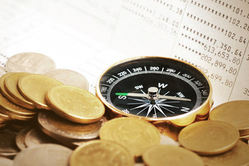 Coins and compass on bank book account in vintage color