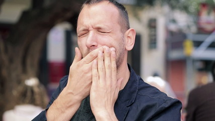 Man having toothache while drinking hot coffee in city